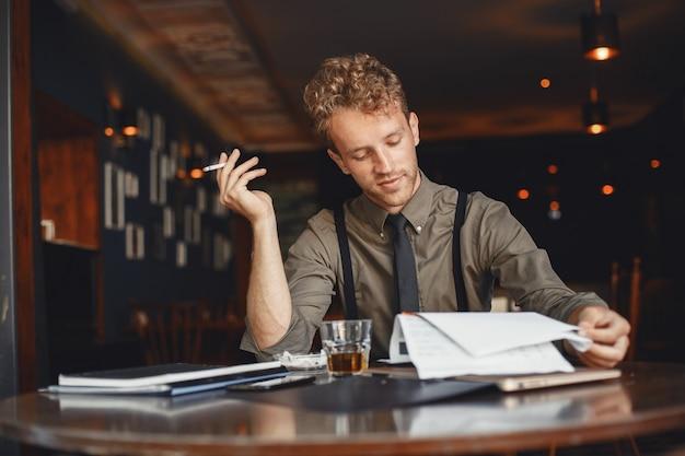 L'uomo beve whisky. l'uomo d'affari legge i documenti. regista in camicia e bretelle.