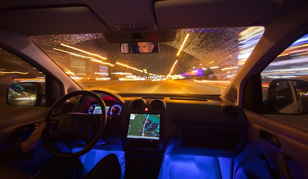 The man drive car in the night city. inside view. wide angle