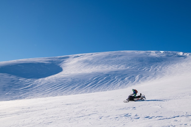 A man drive  snowmobile  in a sunny day, iceland