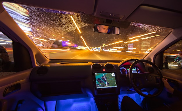 The man drive with navigation in the night city. left side traffic. wide angle