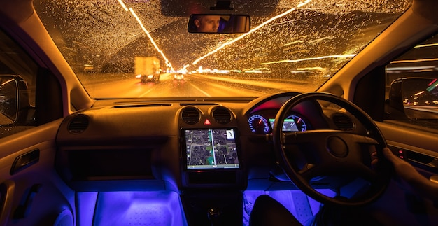 The man drive with navigation in the rainy city. evening night time