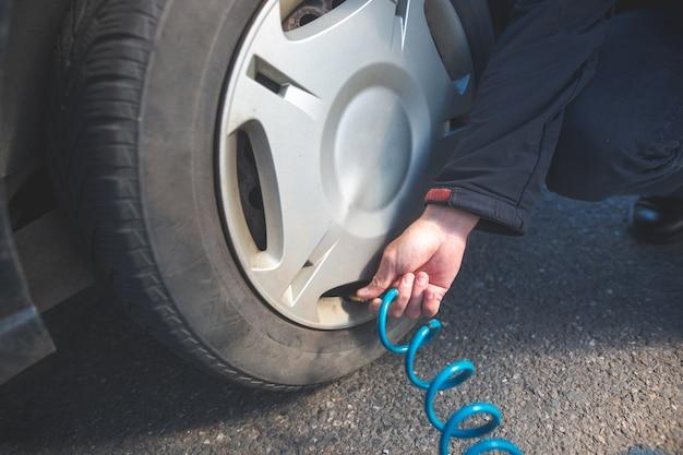 Водитель человека проверяет давление воздуха и заполняет воздухом шины своего современного автомобиля, транспортную концепцию