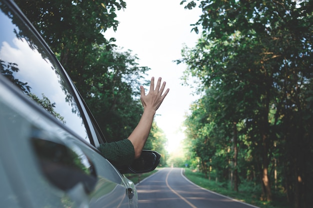 Man driver feeling the wind through his hands while driving in the country side