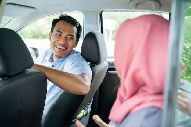 Man driver looks smile and happy chatting with a hijab passenger