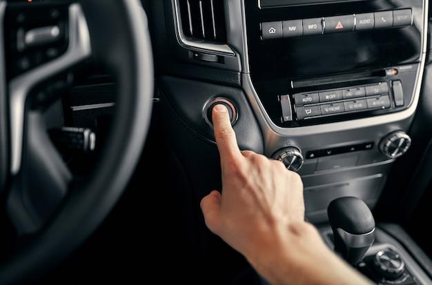 現代の高級車のスタートイグニッションボタンスイッチを押す男性ドライバー。