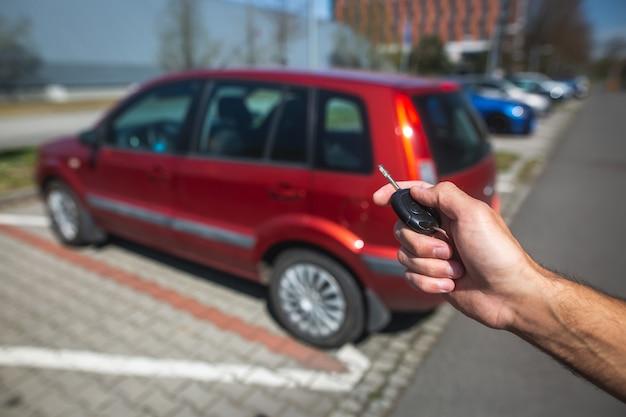 Водитель человек, дистанционно отпирающий автомобиль ключом от машины, транспортная концепция