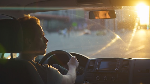 The man drives the car on highway on the sunset sky background