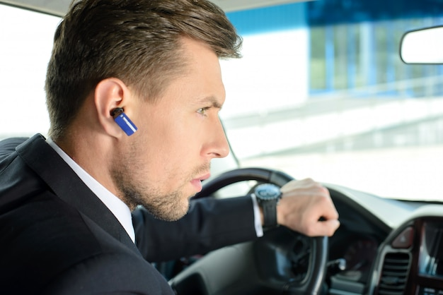A man drives a car and speaks on bluetooth.