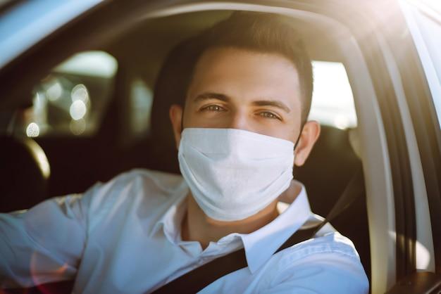 Мужчина за рулем автомобиля надевает медицинскую маску во время эпидемии в карантинном городе.