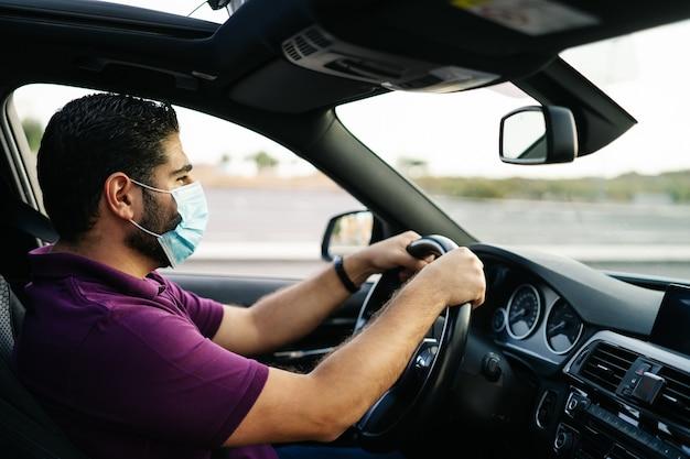 Covid 전염병 동안 의료 마스크를 쓰고 차를 운전하는 남자. 코로나 바이러스 개념.