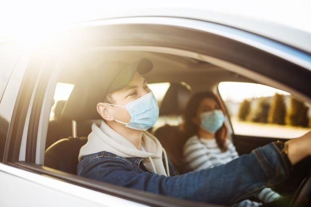 滅菌医療マスクを着用して車を運転する男
