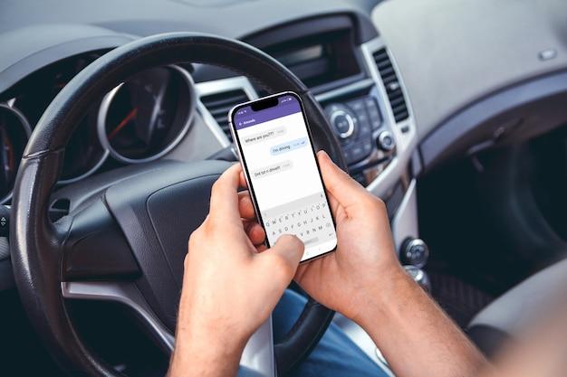 그의 손에 전화로 차를 운전하는 남자. 문자 및 운전 금지