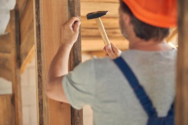 木製の梁にハンマーで釘を打ち込む男