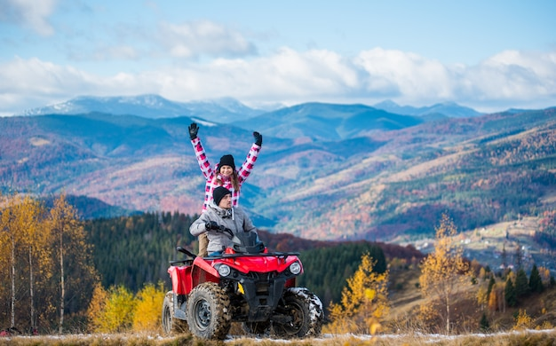 Man driving atv quad bike, woman sitting behind him and raised her hands up on a mountain road