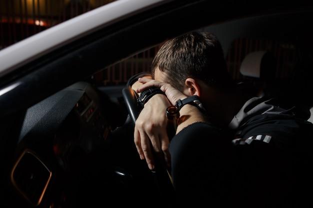 Человек за рулем автомобиля и засыпает за рулем