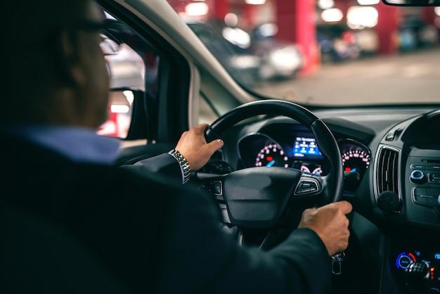 밤에 차를 운전하는 남자, 바퀴에 손. 뒷좌석에서 찍은 사진.
