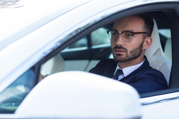 車を運転する男。朝に車を運転する眼鏡をかけている暗い目のハンサムなビジネスマン