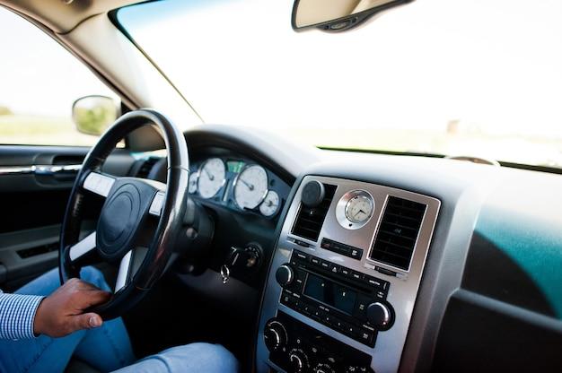 Man driving car, hand on steering wheel.