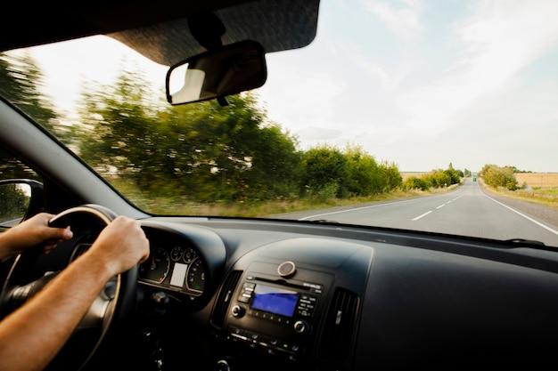 Человек за рулем автомобиля на дороге Premium Фотографии