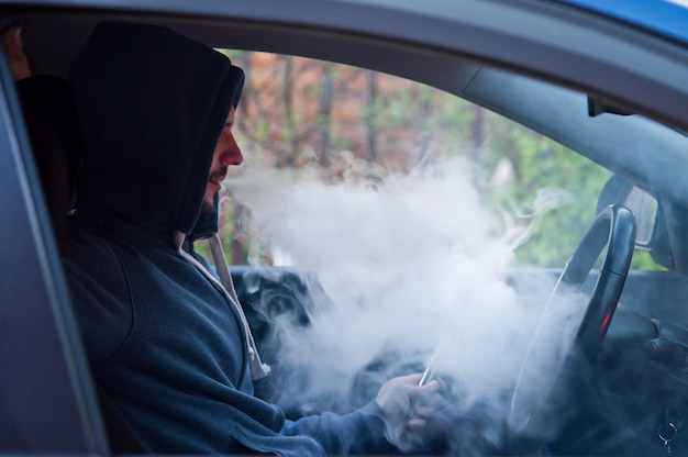 Man driving a car smokes an electronic cigarette.