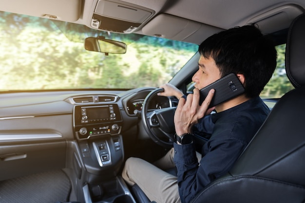 Man driving a car and talking on a mobile phone