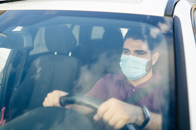 Man driving a car wearing on a medical mask during a covid pandemic. coronavirus concept.
