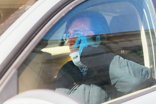 A man driving in a car with a protective mask and gloves is talking on the phone, epidemia of coronavirus. work during quarantine