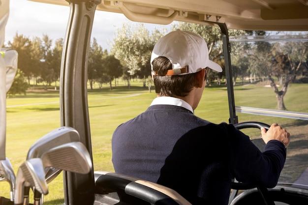 필드에 골프 카트를 운전하는 남자