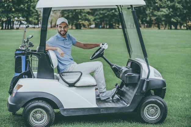 Человек за рулем тележки для гольфа. вид сбоку красивого молодого человека, управляющего тележкой для гольфа и смотрящего в камеру