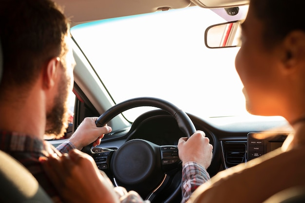 彼のガールフレンドの隣で運転している男