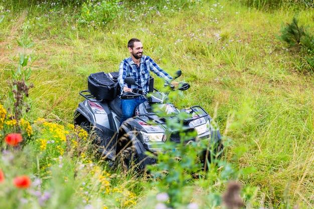 クワッドバイクまたはatvでオフロード運転の男