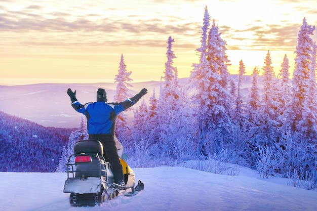 Man driving snowmobile in snowy forest.