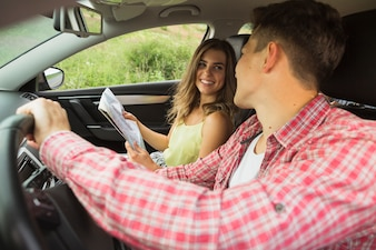 Man driving the car looking at woman holding map