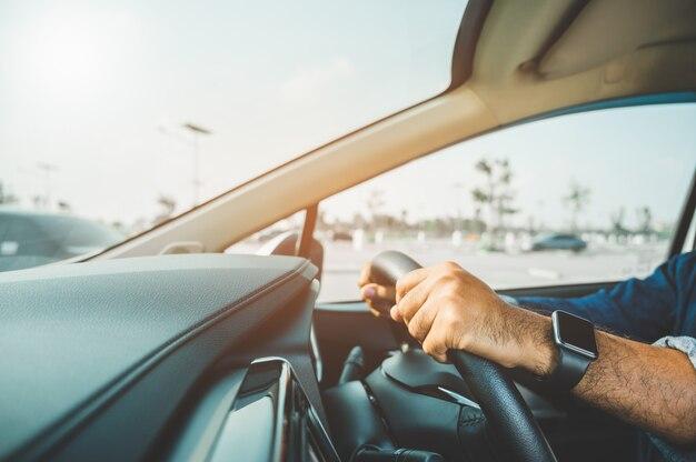 時計を手にして車を運転する男