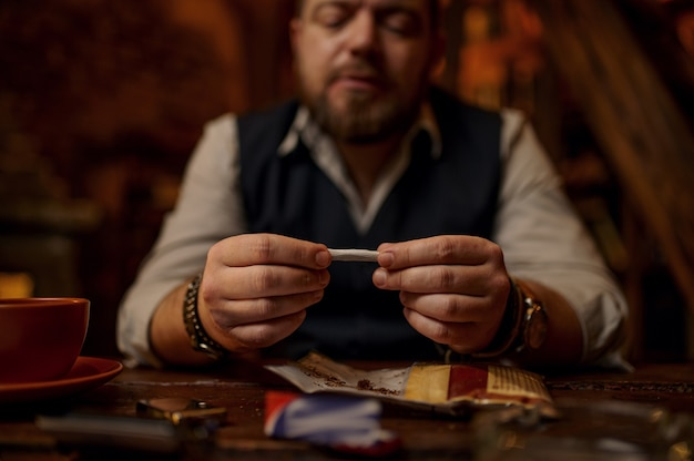 Man drooling hand-rolled cigarette, wooden table on background. tobacco smoking culture, specific rich flavor. male smoker leisures in office