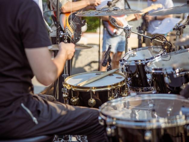 Man drummer having concert rehearsal on the street
