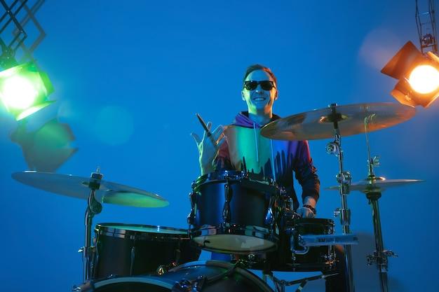 Man drummer playing on neon light