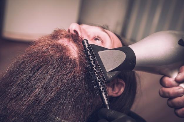 Man drying his beard at the barber .