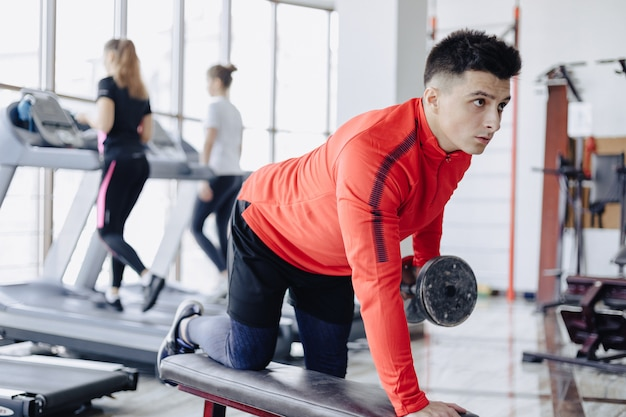 A man dumps triceps on the background of treadmills
