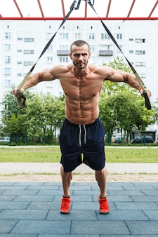Man during workout with suspension straps