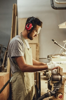 Man in earmuffs working on belt sander