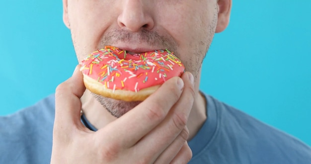 Man eat donut closeup on blue