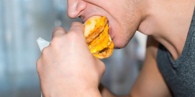 コートレット、チーズ、目玉焼き、クローズアップで大きなハンバーガーを食べる男。