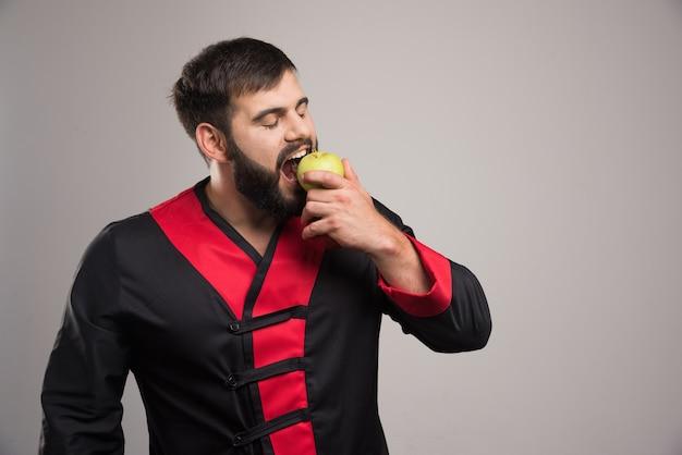 緑の新鮮なリンゴを食べる男。