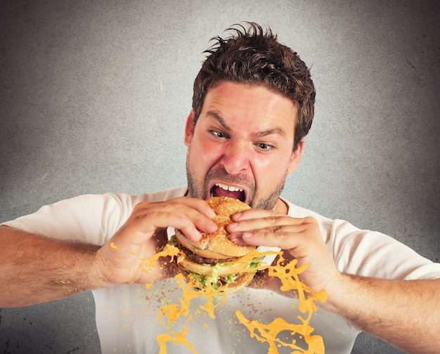 Человек ест бутерброд с бешеной порывом