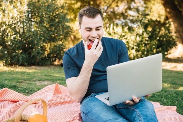 Man eating apple e usando il portatile