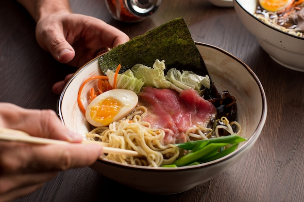 レストランでマグロと麺とアジアのラーメンを食べる男