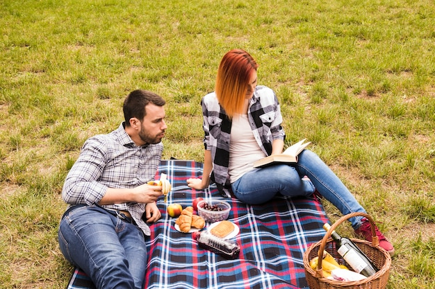 Man eating banana looking at her girlfriend reading book at the picnic