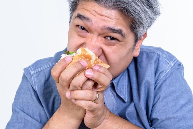 空腹のハンバーガーからパンを食べる男