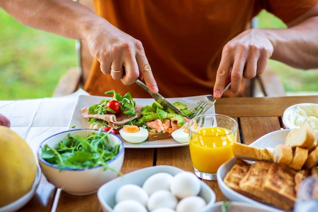 朝食のトーストと卵を食べる男性朝食にトーストホテルでの朝食家庭料理の健康